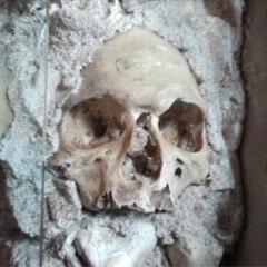 Foto de um crânio preso a um pilar na Capela dos Ossos